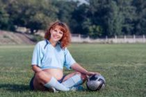 Young pregnant woman dressed in soccer uniform
