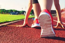 Female athlete on the starting line of a stadium track preparing for a run