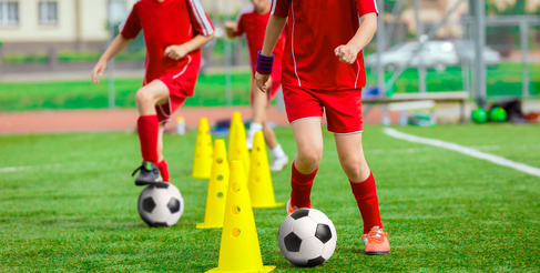 Soccer Ball and Pylons on Grass. Youth Soccer Player Training. Young Footballer with Ball Training with Cones