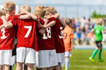 Boys Soccer Team. Children Football Academy. Kids Soccer Players in Red Shirts Standing Together on the Pitch. Youth Soccer Motivational Speech. Coach Motivational Talk With Young Boys